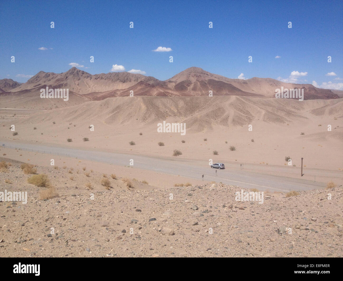 USA, Nevada, Car parked on empty desert road - Stock Image
