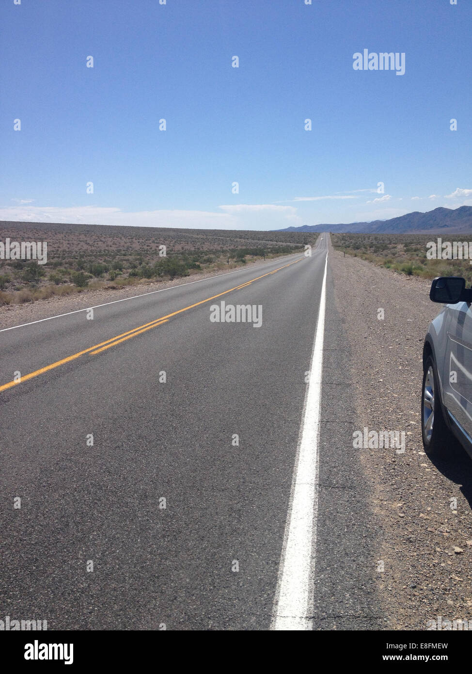 USA, Nevada, Infinity road with car parked on roadside - Stock Image