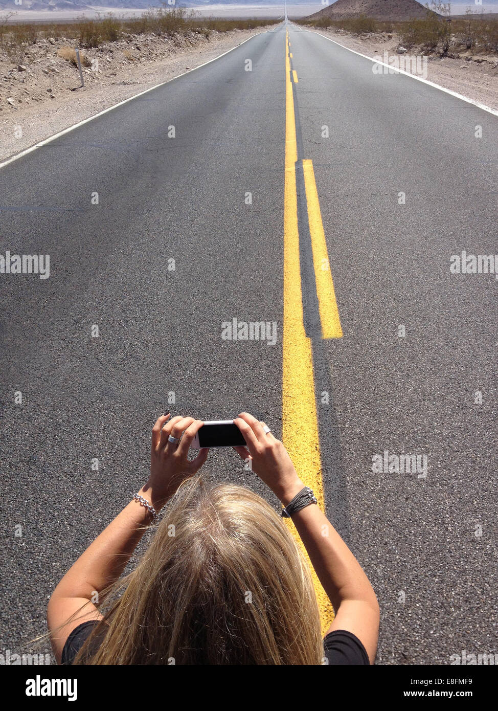 Woman taking photo of infinity road with mobile phone, Nevada, America, USA - Stock Image