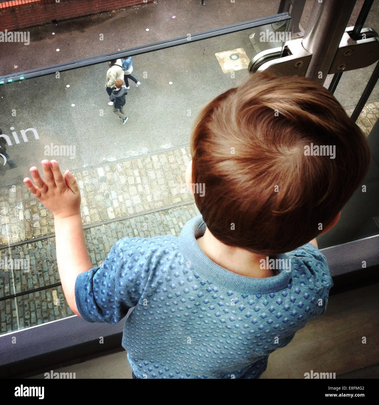 United Kingdom, England, Manchester, Child watching people from above - Stock Image