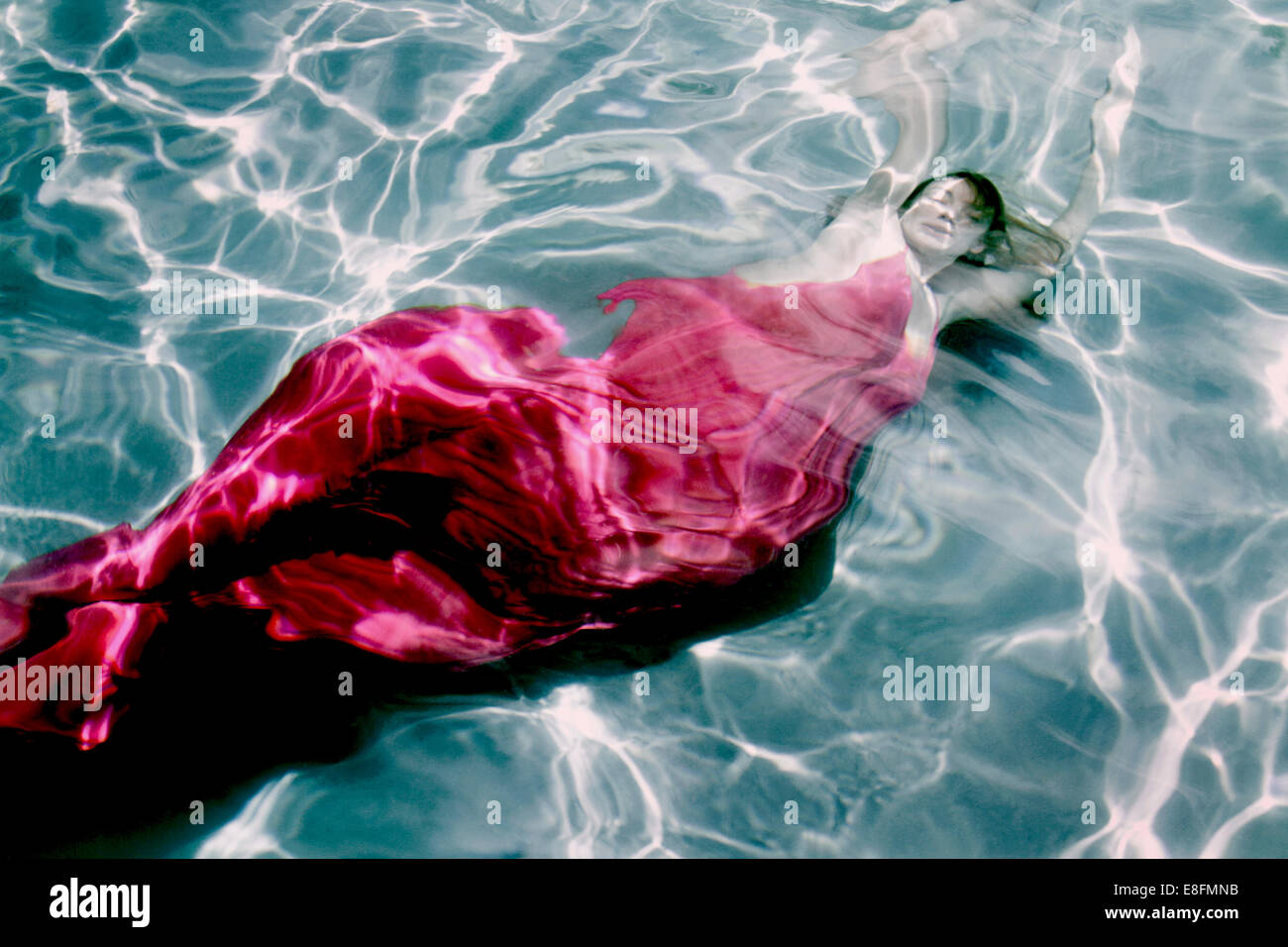 Woman in dress underwater - Stock Image