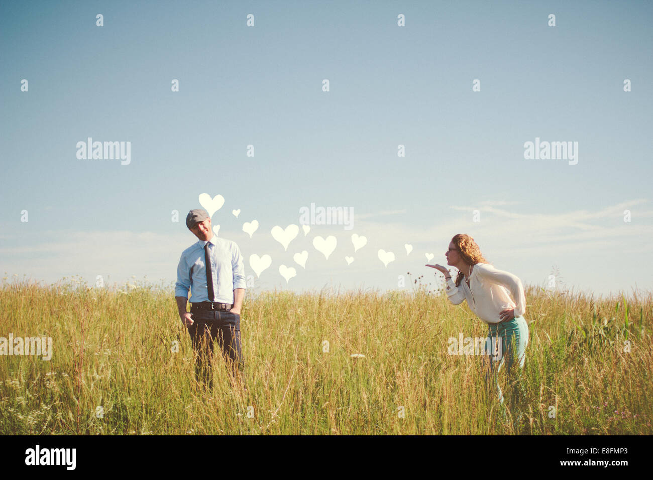 USA, Tennessee, Davidson County, Nashville, Couple blowing hearts on meadow - Stock Image