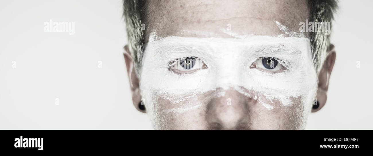 Studio shot of man's face with painted goggles - Stock Image