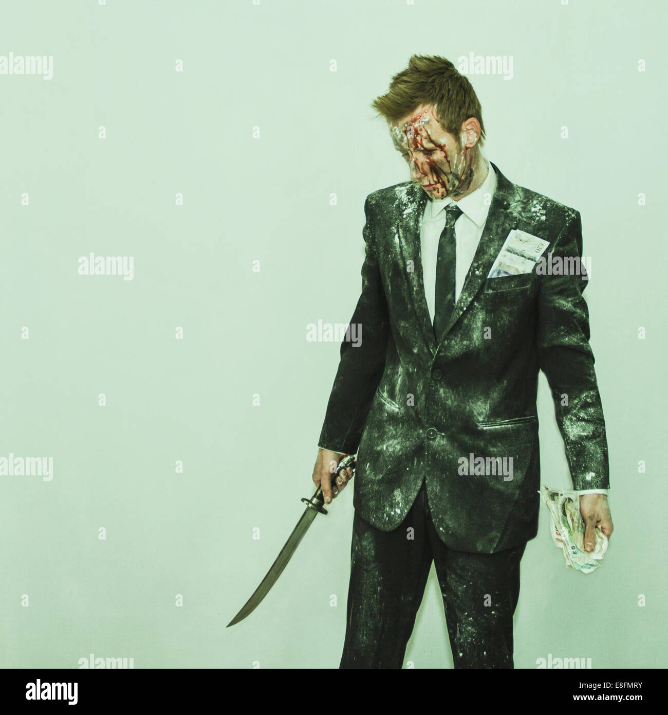 Man in suit holing sword and money - Stock Image
