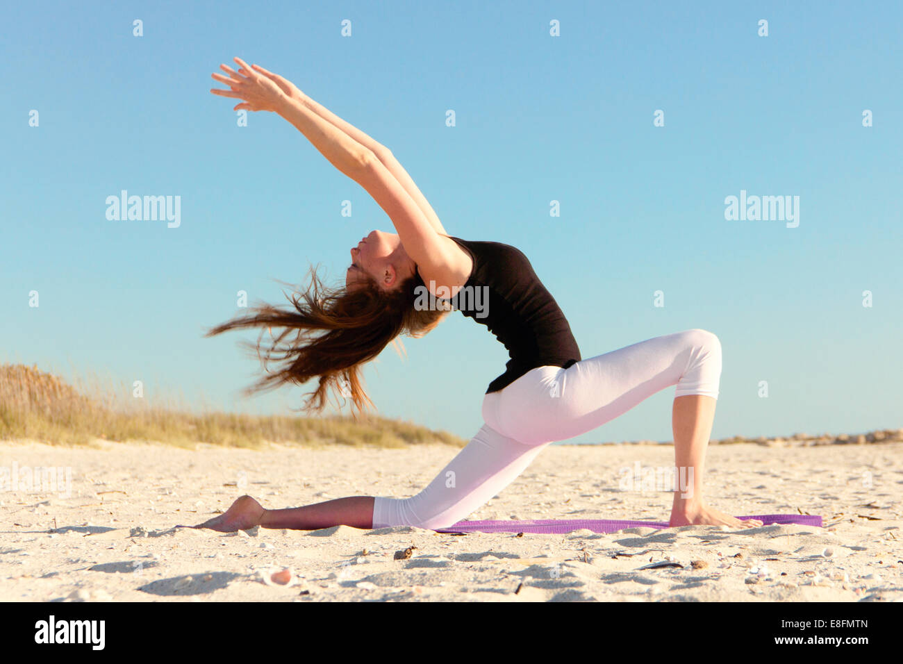 Woman doing yoga on beach - Stock Image