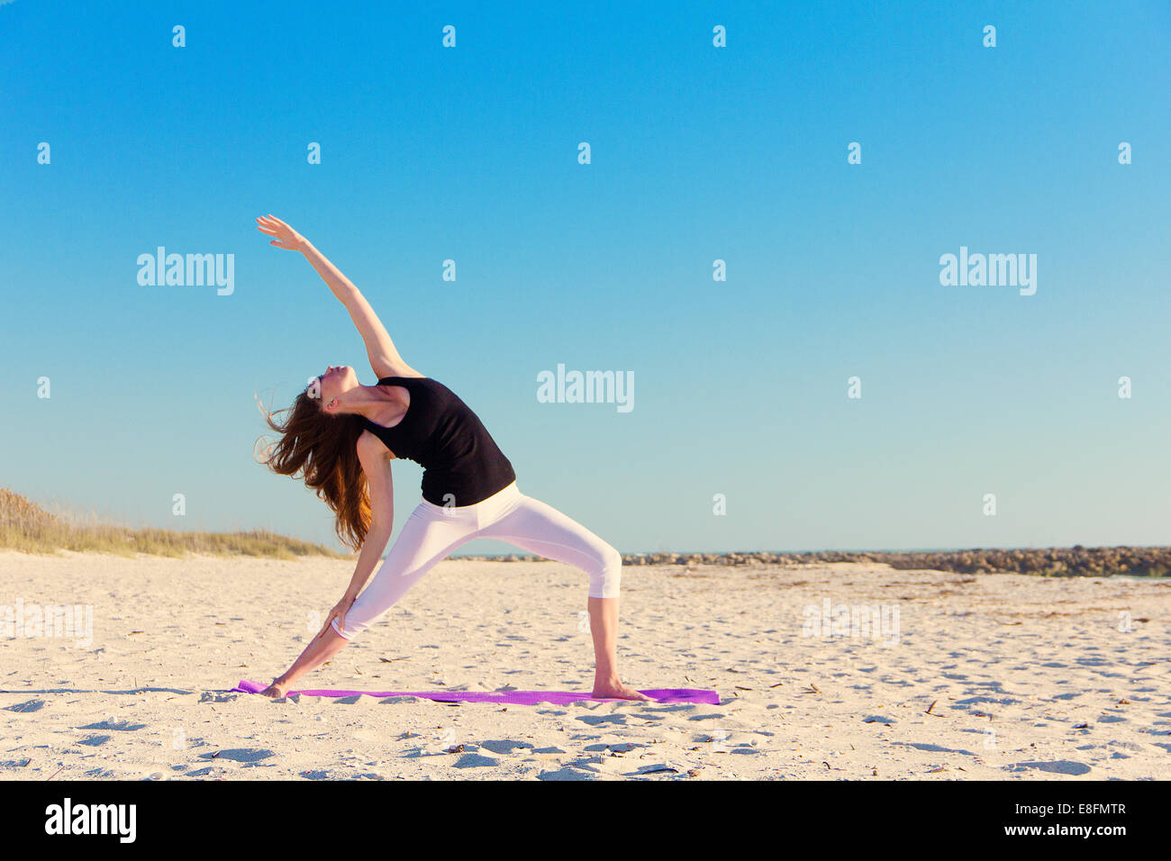 Woman practising reverse warrior pose on beach - Stock Image