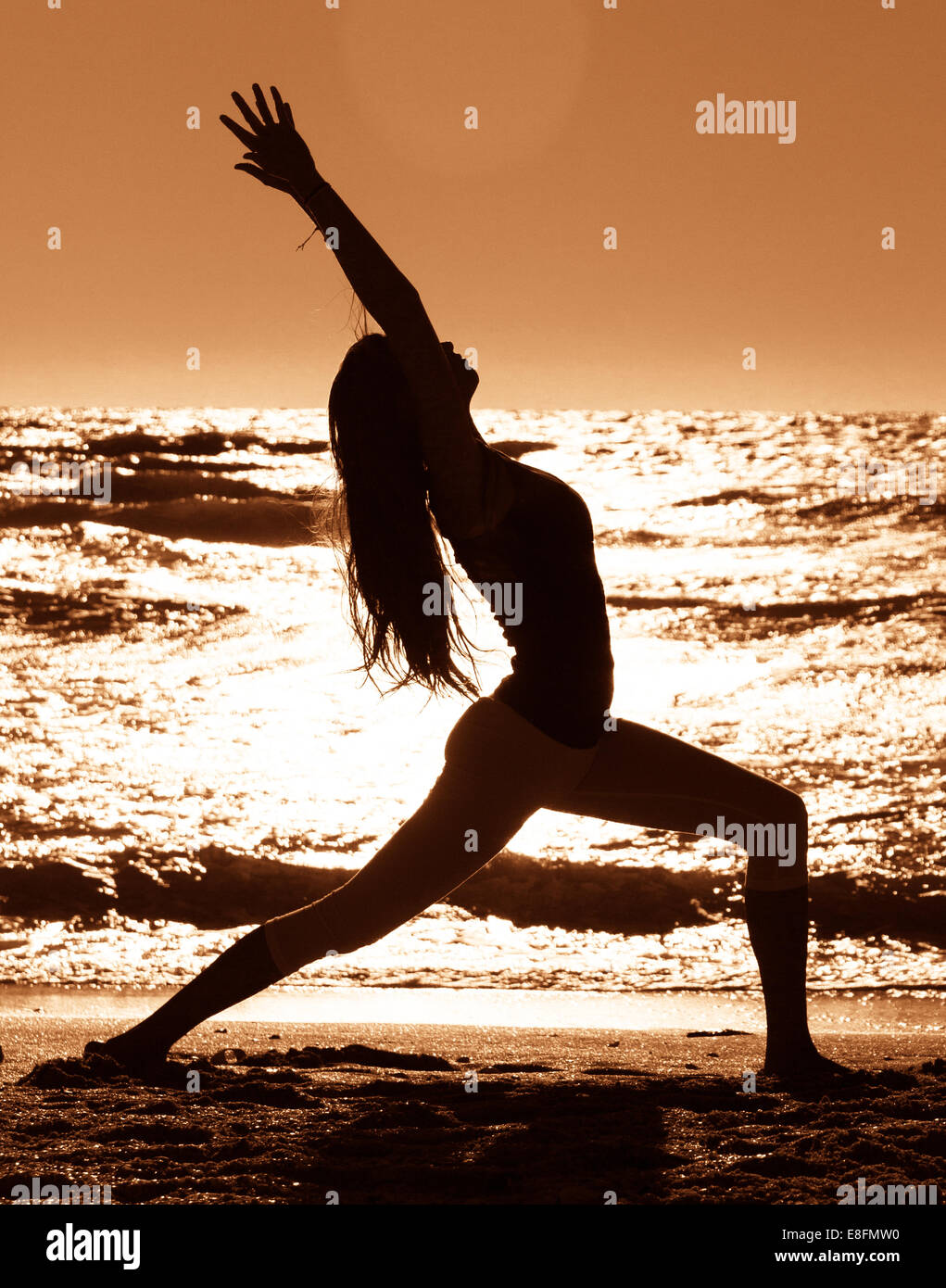 Silhouette Of Woman Practicing Warrior 1 Yoga Pose On Beach