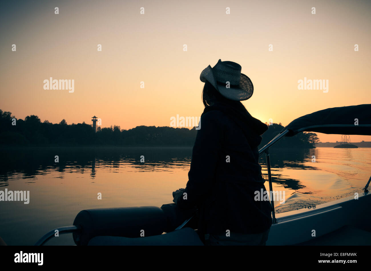 Silhouette of woman on boat looking at view - Stock Image