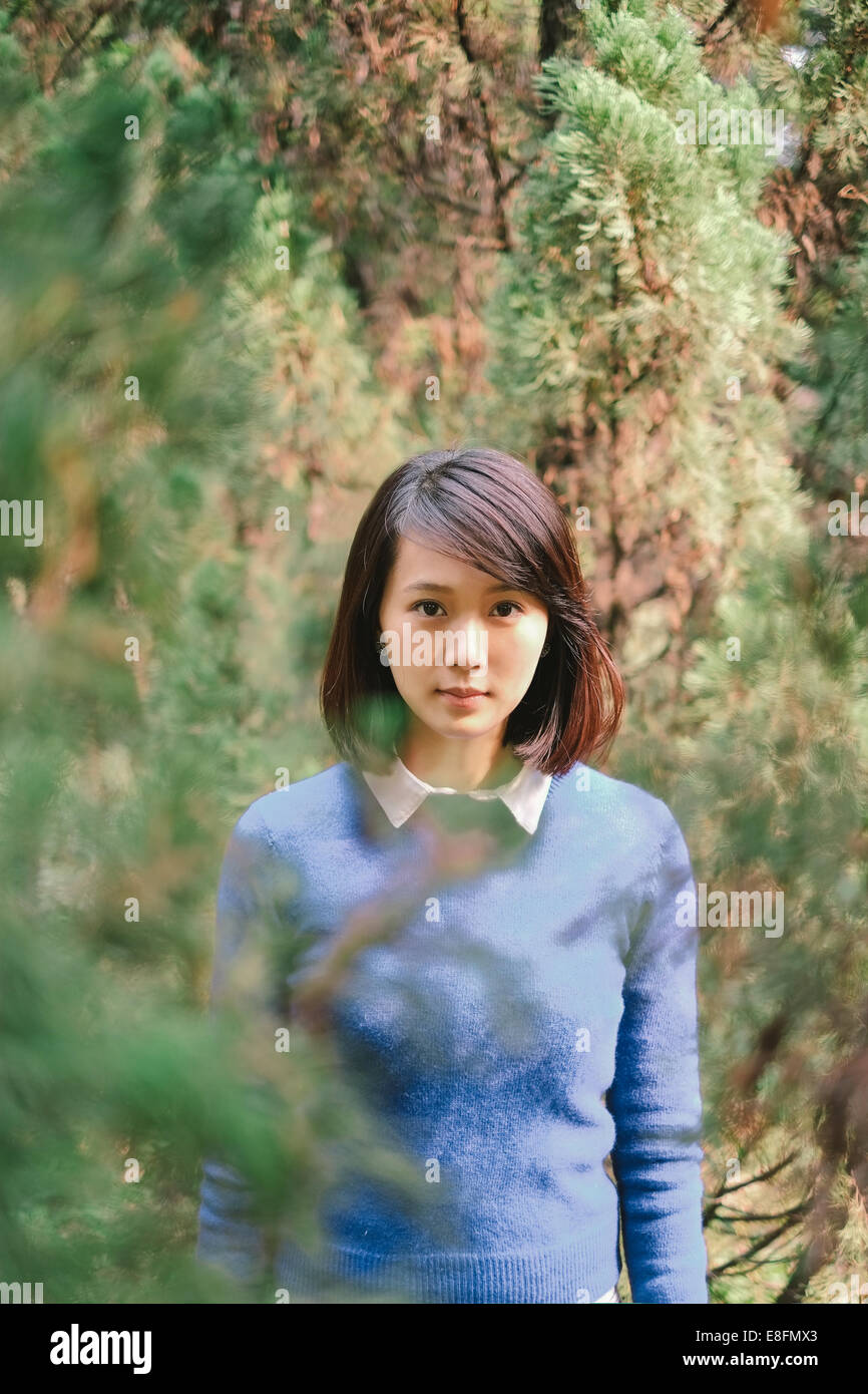 Woman amongst trees in forest - Stock Image