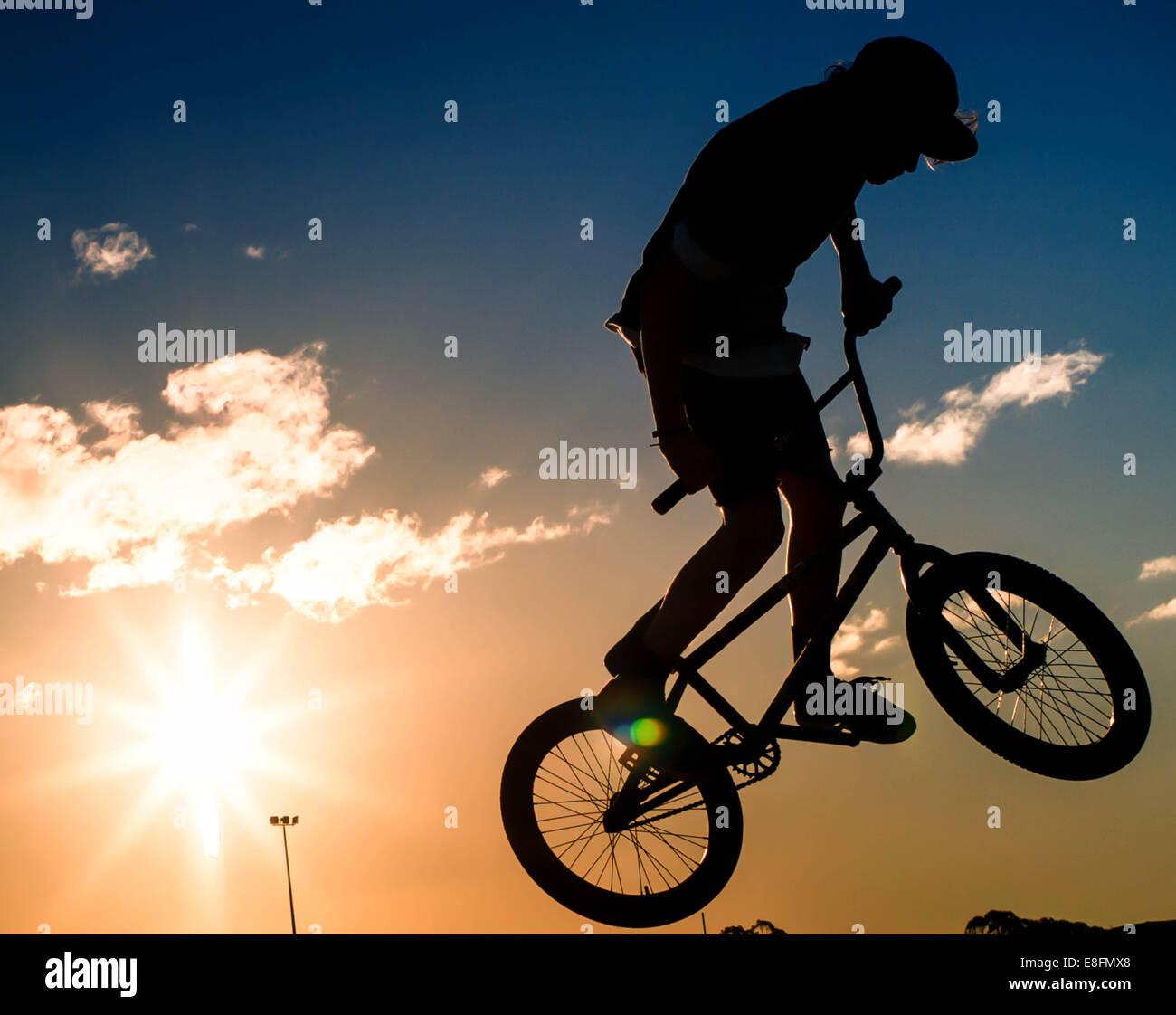 Silhouette of boy doing stunts on his bmx bike - Stock Image