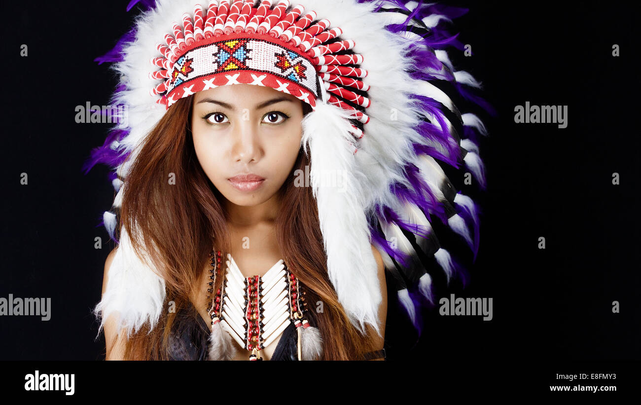 Studio portrait of woman wearing Native American headdress - Stock Image
