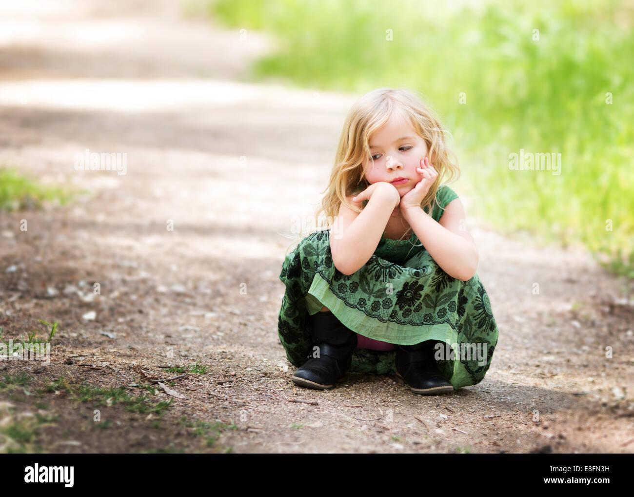 Girl (4-5) crouching on path - Stock Image