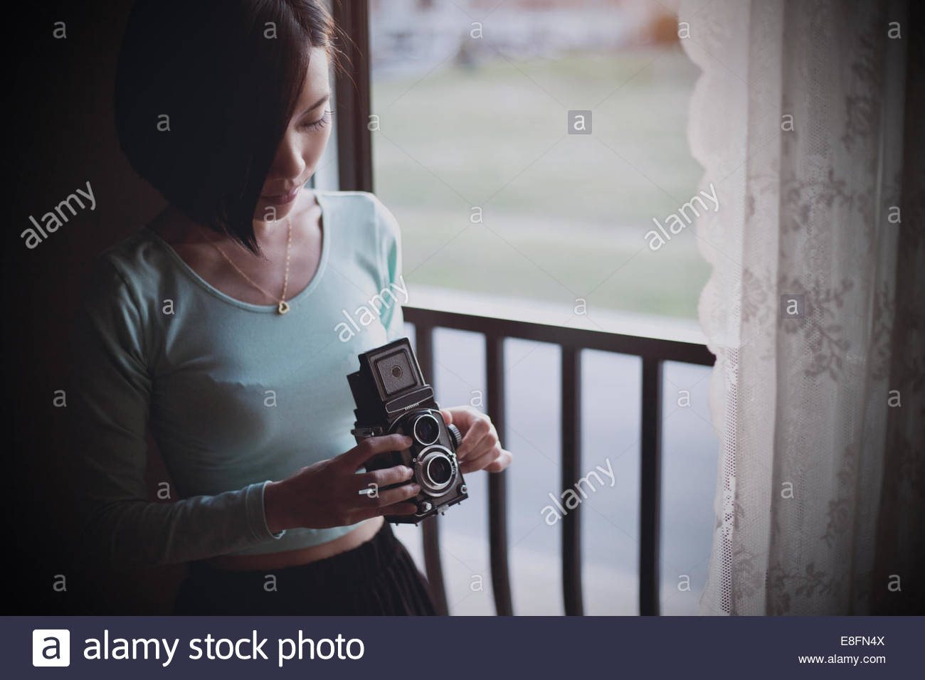 Young woman holding vintage camera - Stock Image