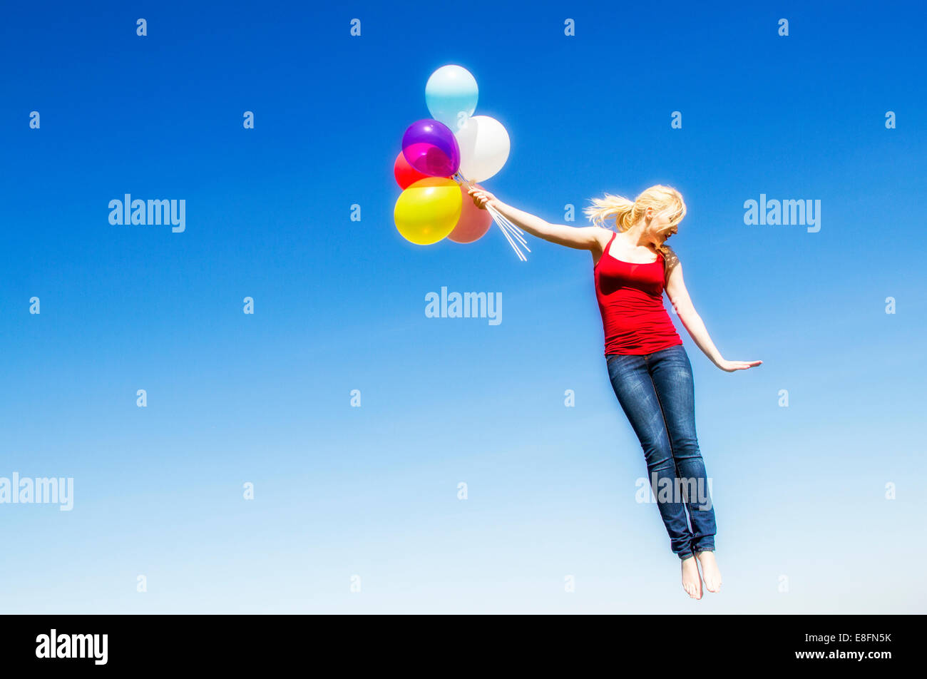 Portrait of flying woman with bunch of balloons - Stock Image