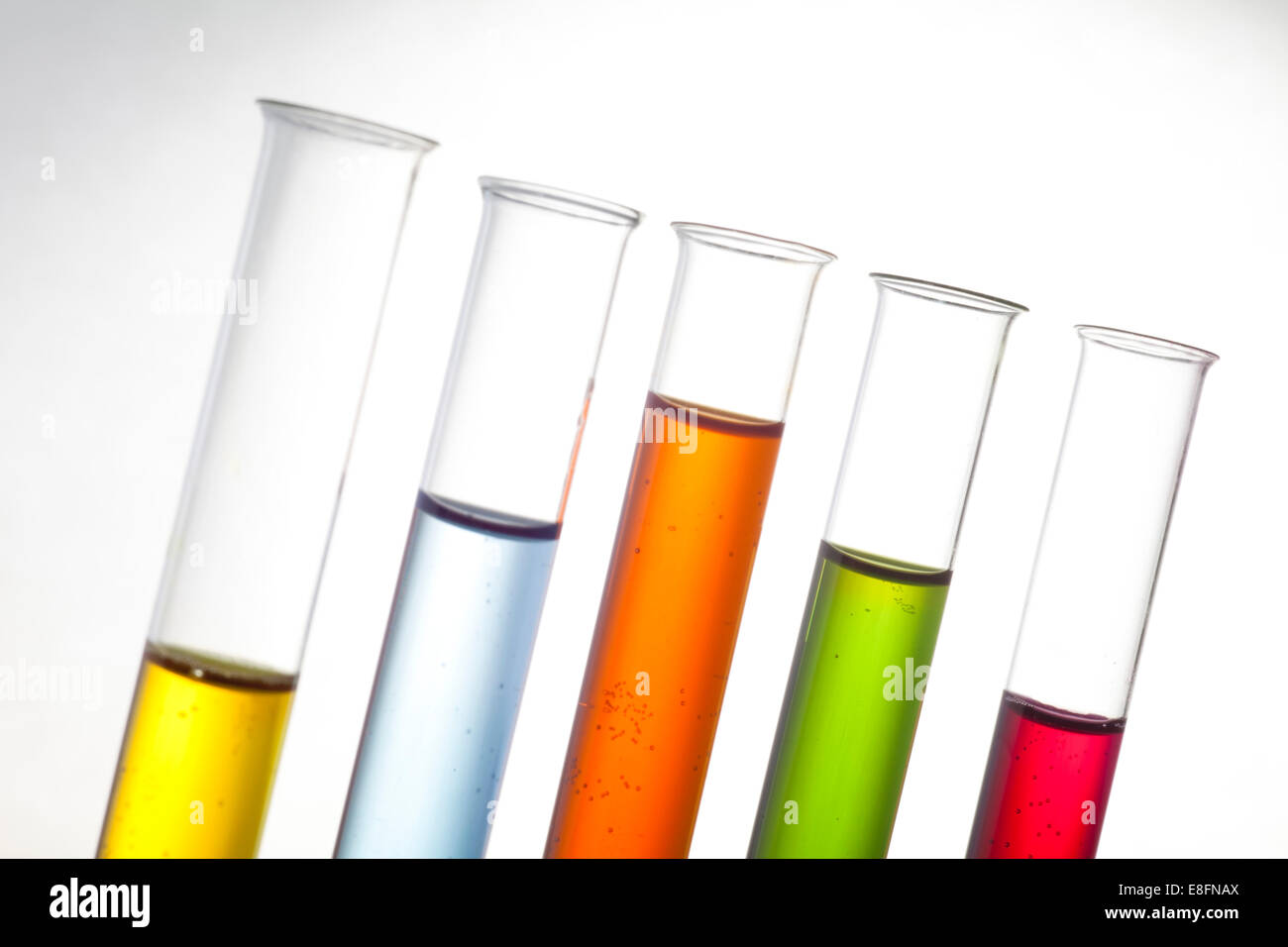 Row of test tubes with multi-colored liquid - Stock Image