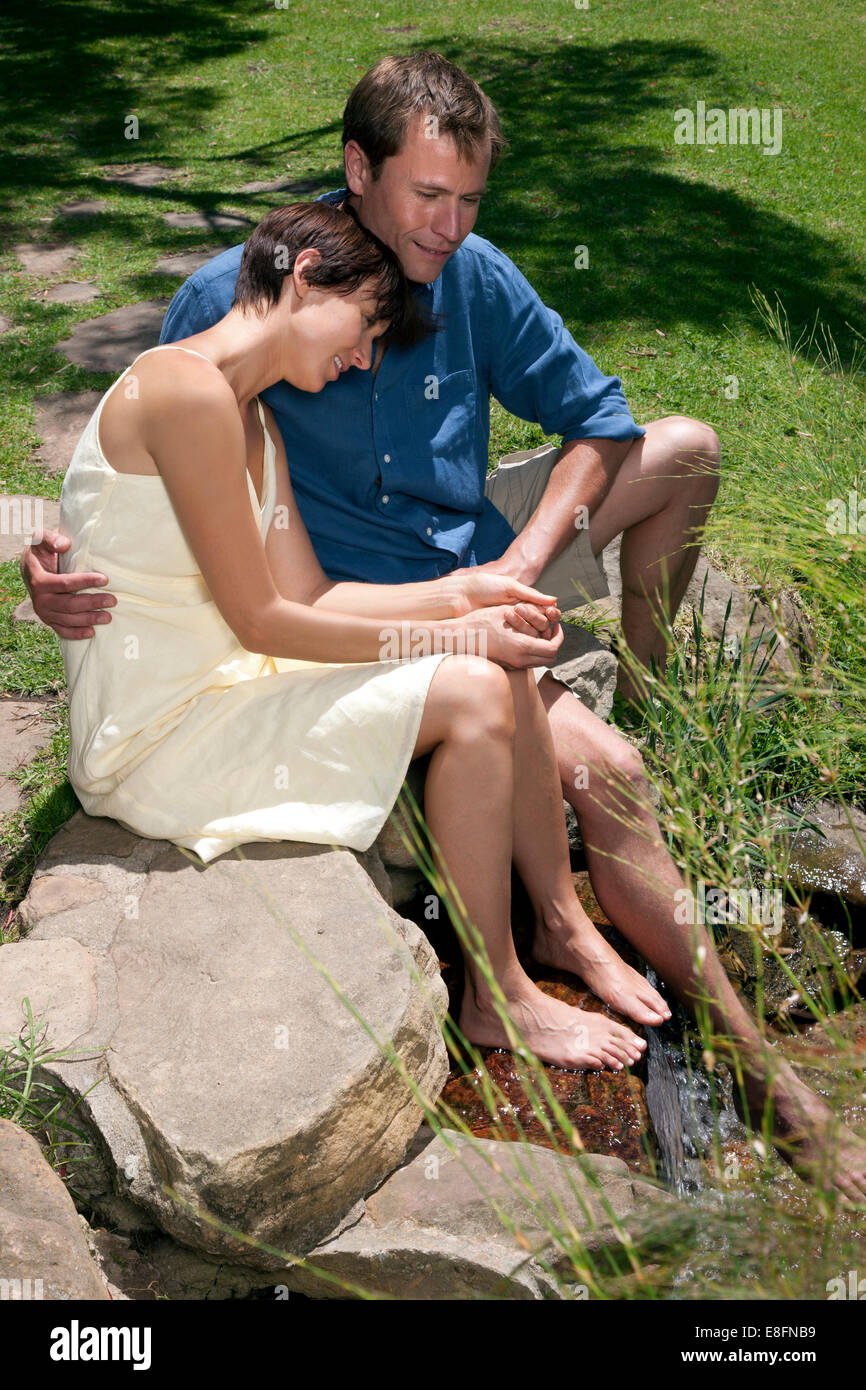 Couple sitting with feet in stream - Stock Image