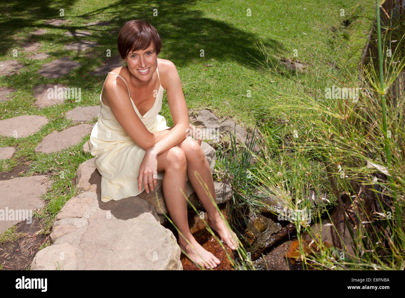 Woman smiling and sitting with feet in stream - Stock Image