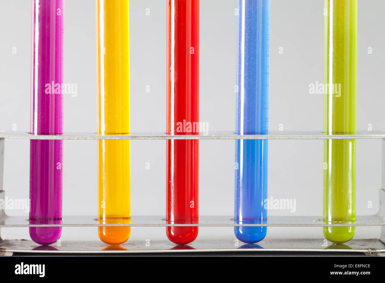 Multi-colored Test tubes in rack - Stock Image
