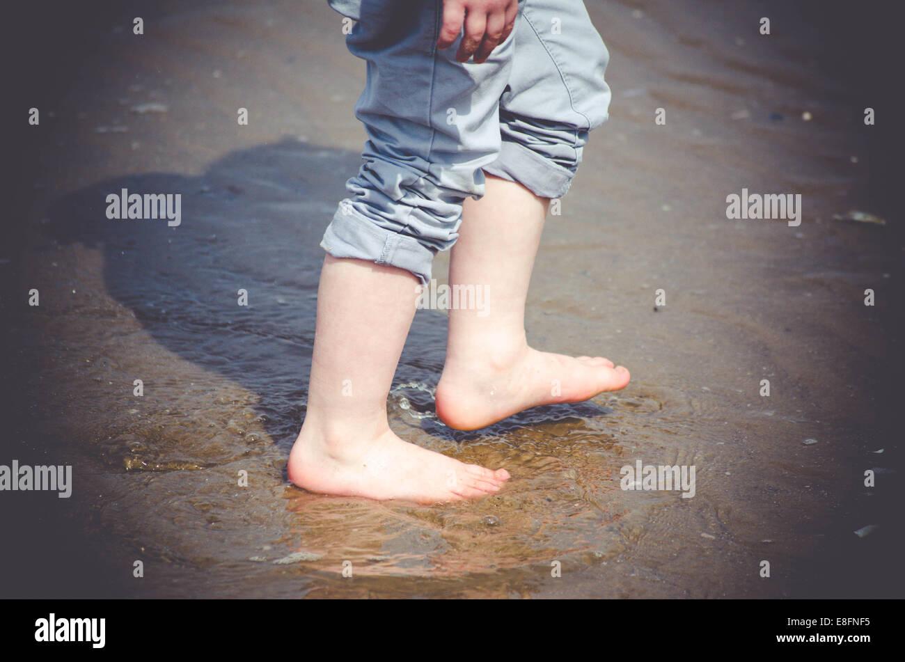 Close-up of boy's legs walking on beach - Stock Image
