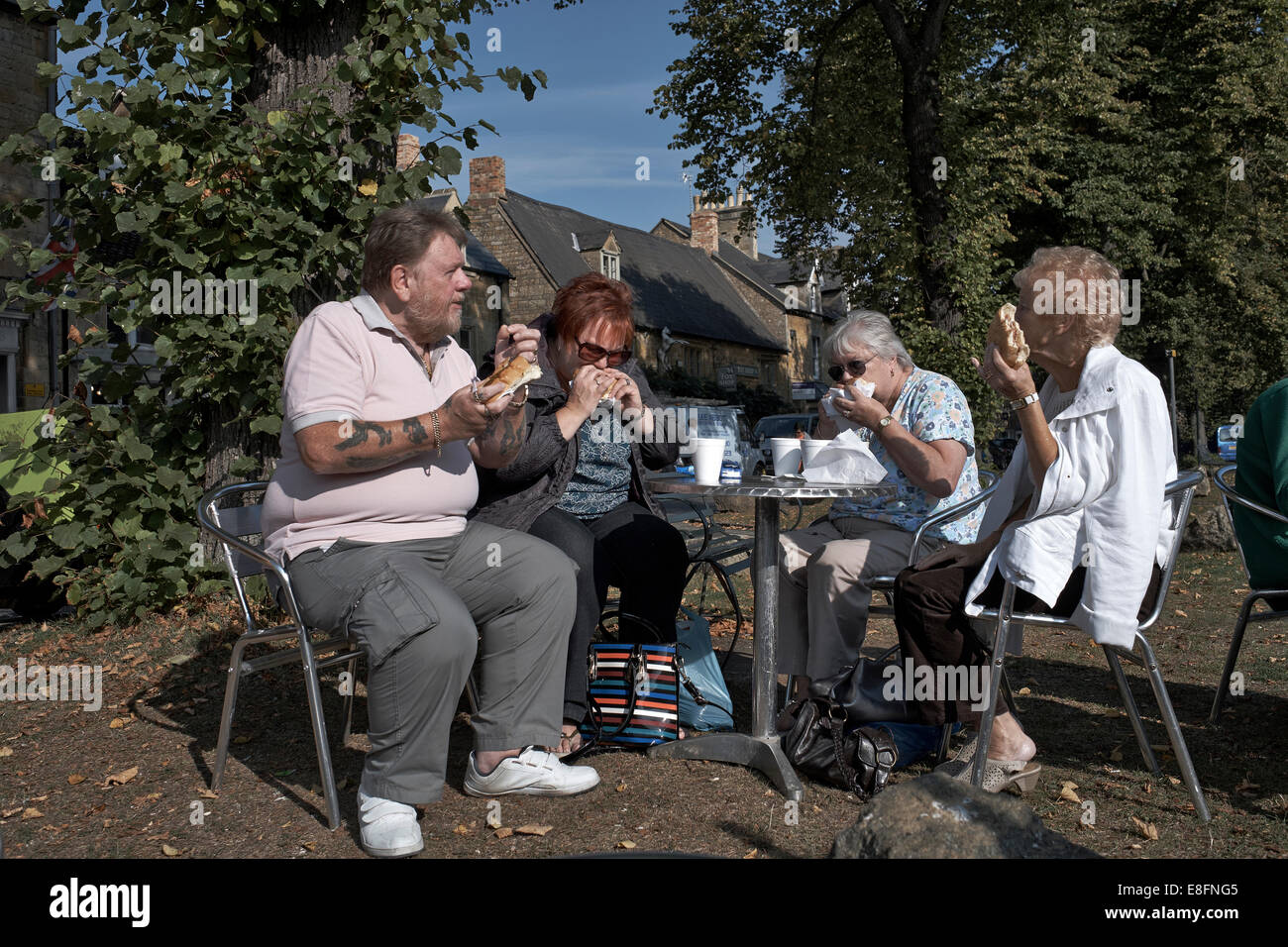 Group of mature English people tucking into unhealthy junk food consisting of burgers and hot dogs at an outdoor - Stock Image