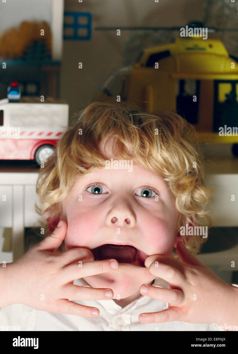 Netherlands, Portrait of boy making funny faces - Stock Image