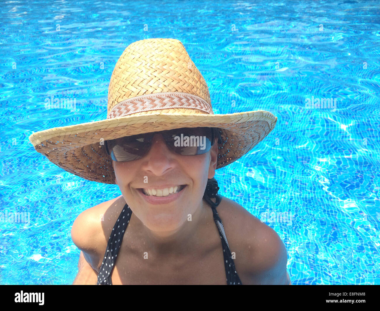 Smiling woman in swimming pool - Stock Image