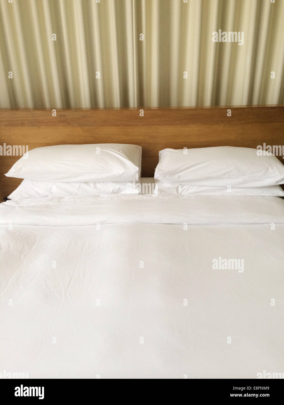 Bed with four pillows and duvet - Stock Image