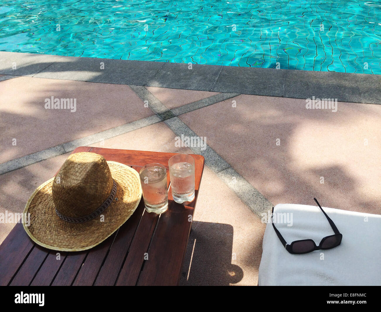 Straw sun hat, sunglasses and two glasses of water by swimming pool Stock Photo