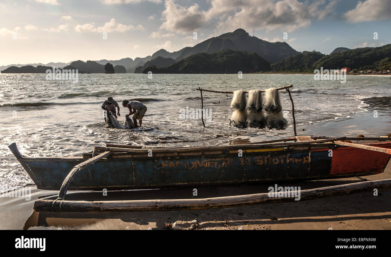 Men tending fishing net - Stock Image