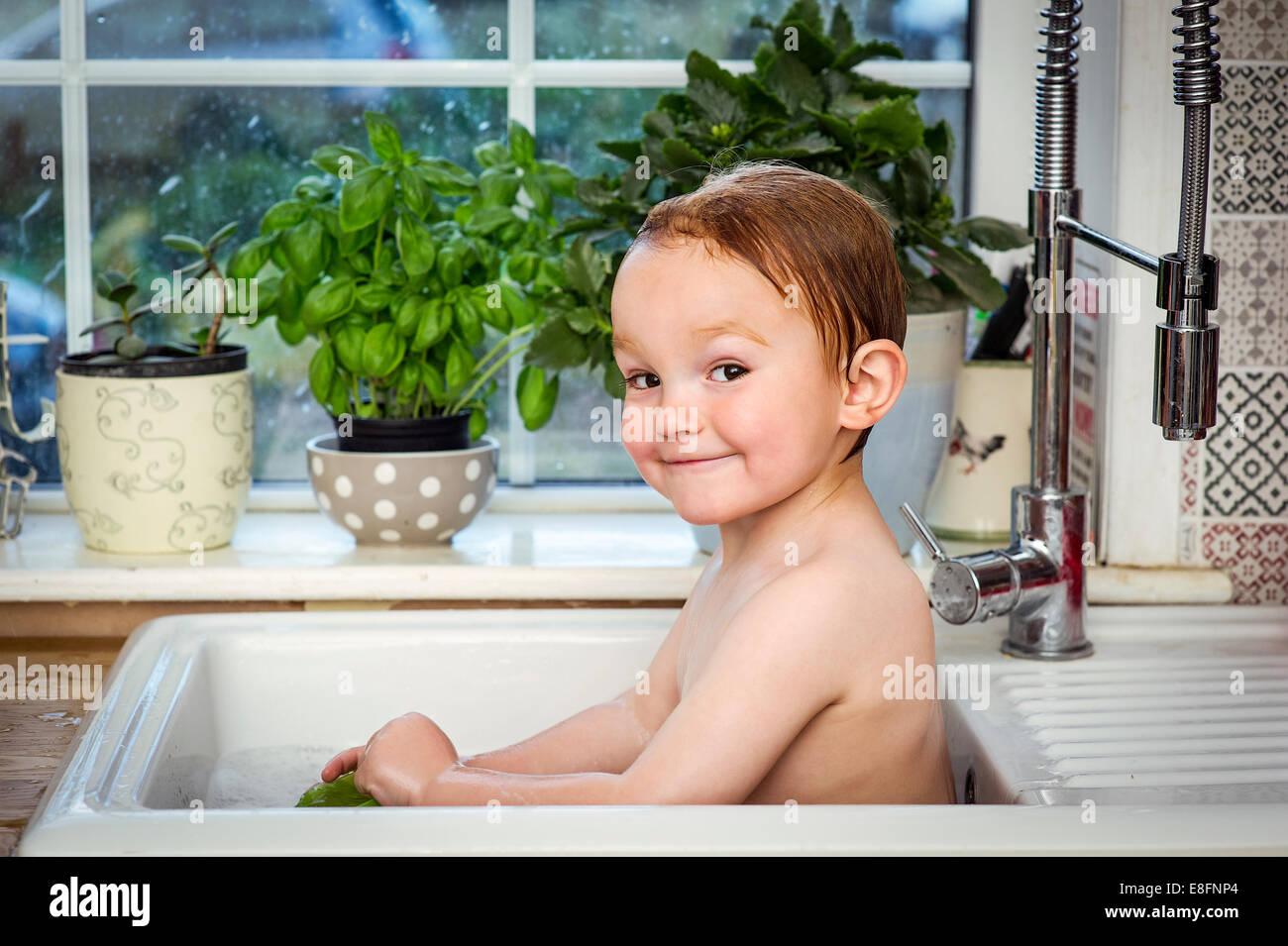 Boy (2-3) taking bath in kitchen sink Stock Photo