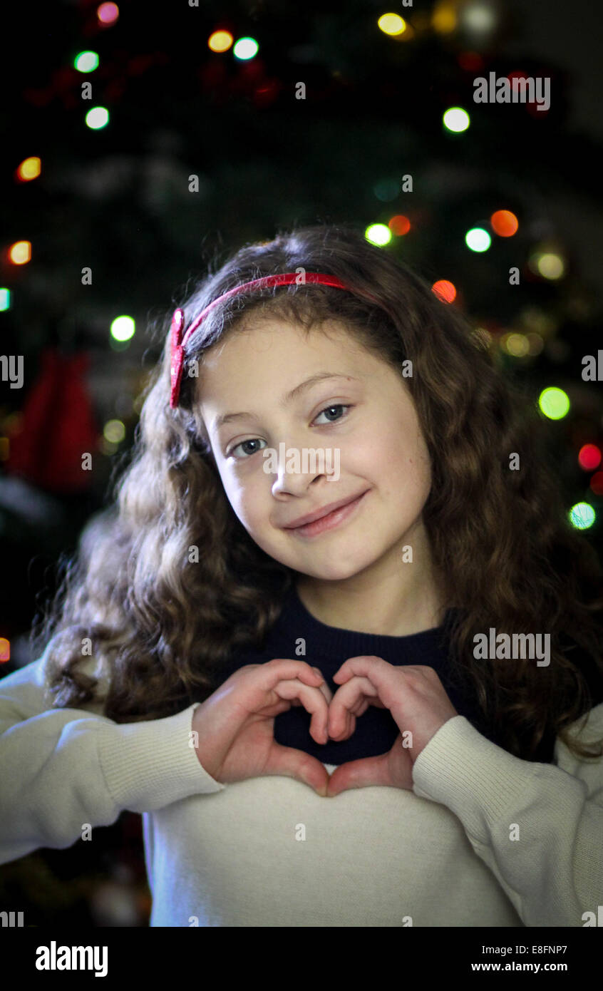 Girl making heart shape with hands in front of Christmas tree - Stock Image
