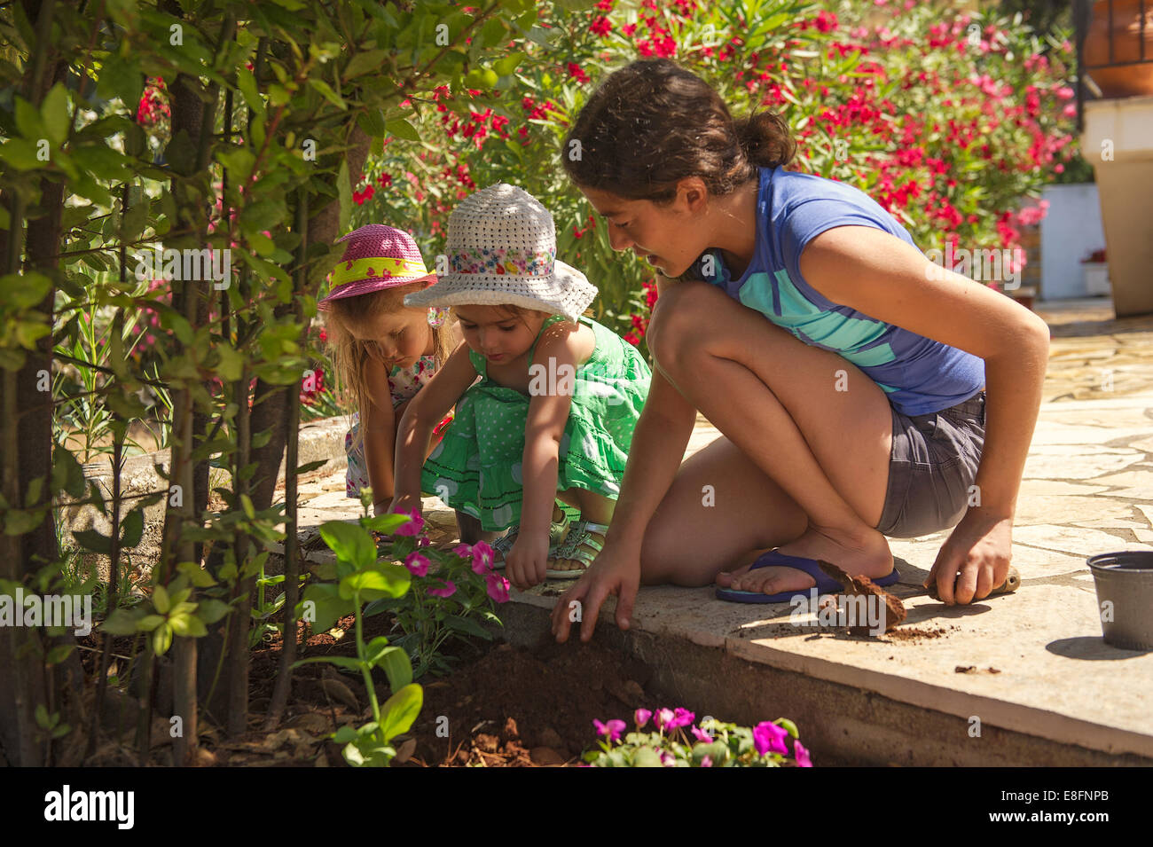 Greece, Ionian Islands Periphery, Kefalonia and Ithaca Prefecture, Mother and daughters (4-5) in garden - Stock Image