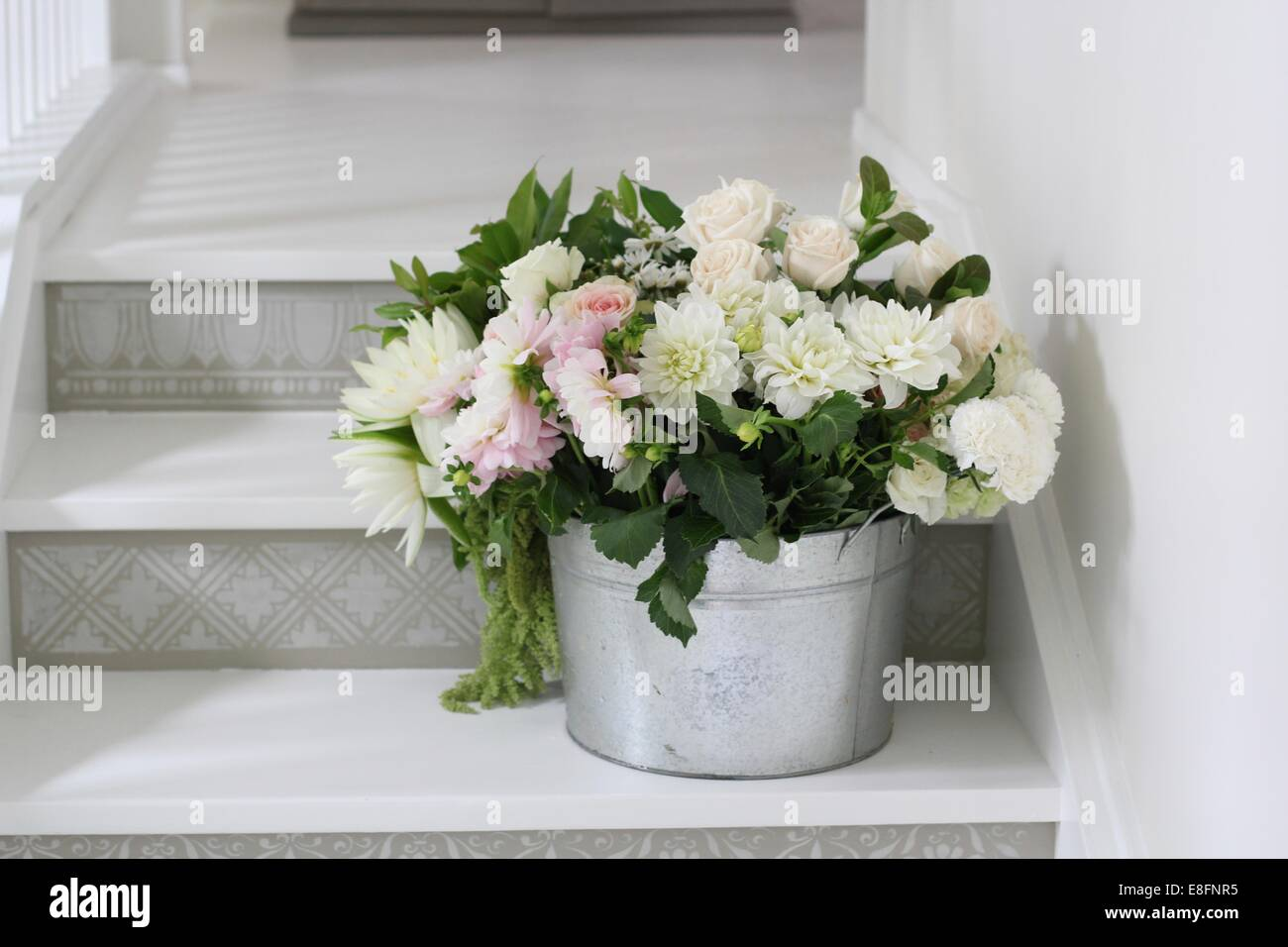Bucket of cut flowers on steps - Stock Image
