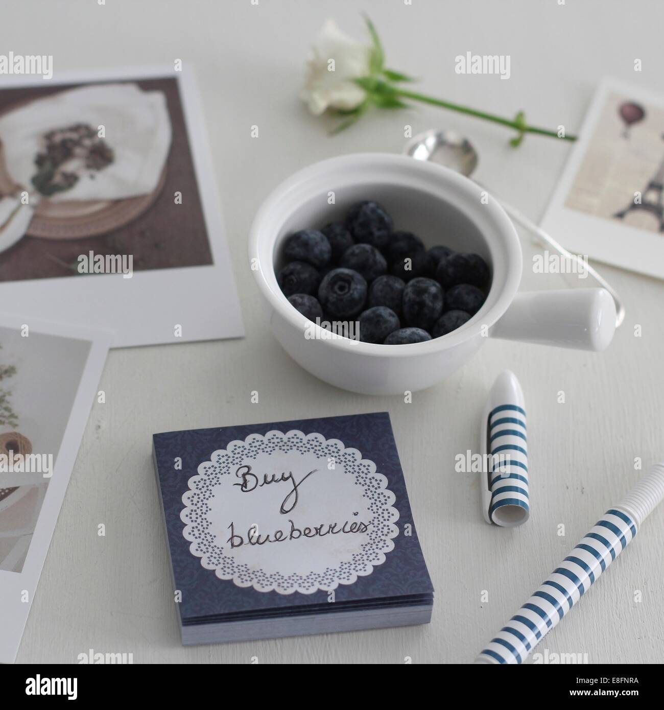 Blueberries in bowl beside hand written memo - Stock Image