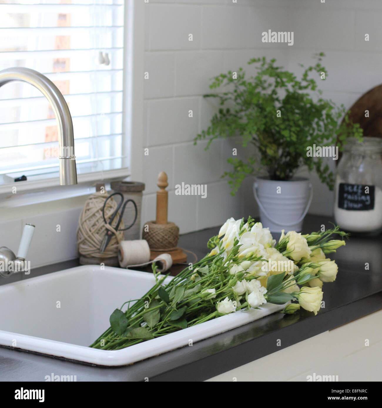 Bunch of flowers in kitchen sink - Stock Image