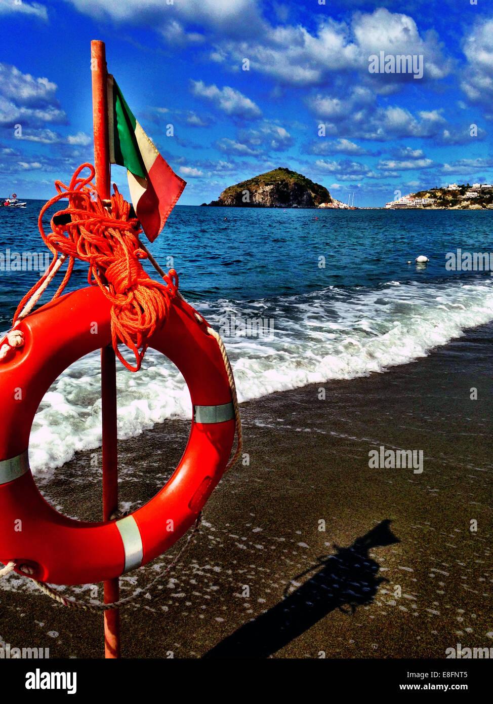 Italy, Ischia, Life preserver on wooden post on beach - Stock Image