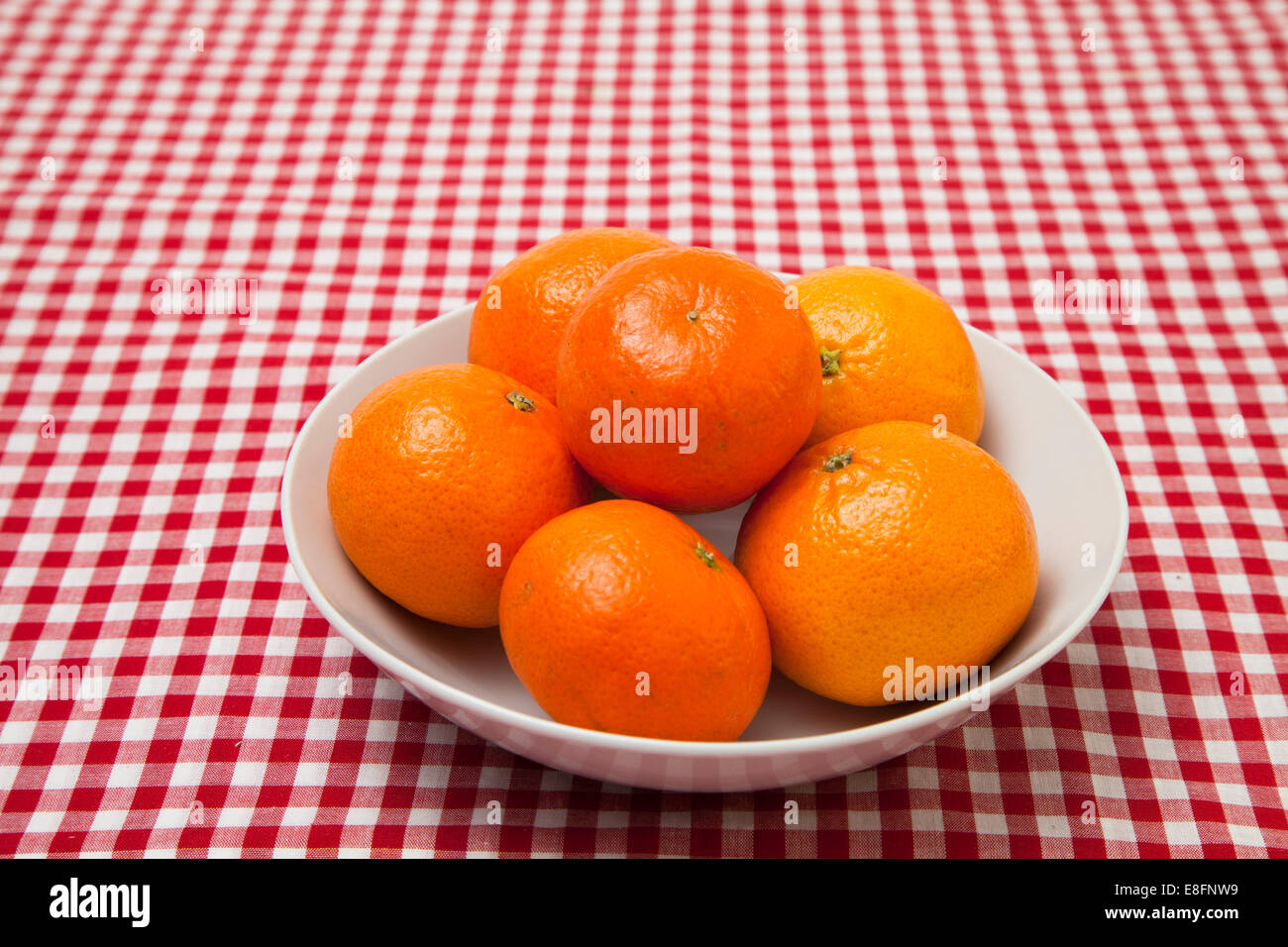 Bowl of oranges on checked tablecloth - Stock Image