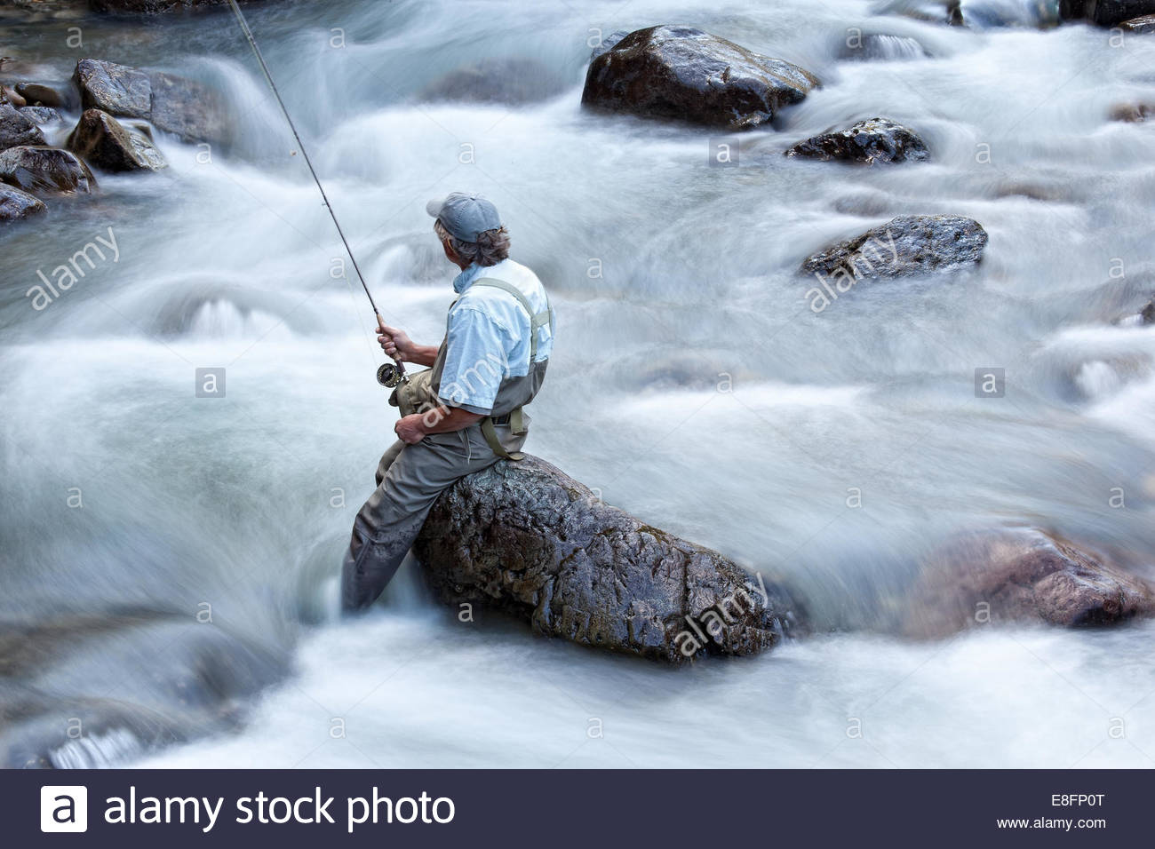 USA, Colorado, Hinsdale County, Lake City, Fisherman sitting on boulder - Stock Image