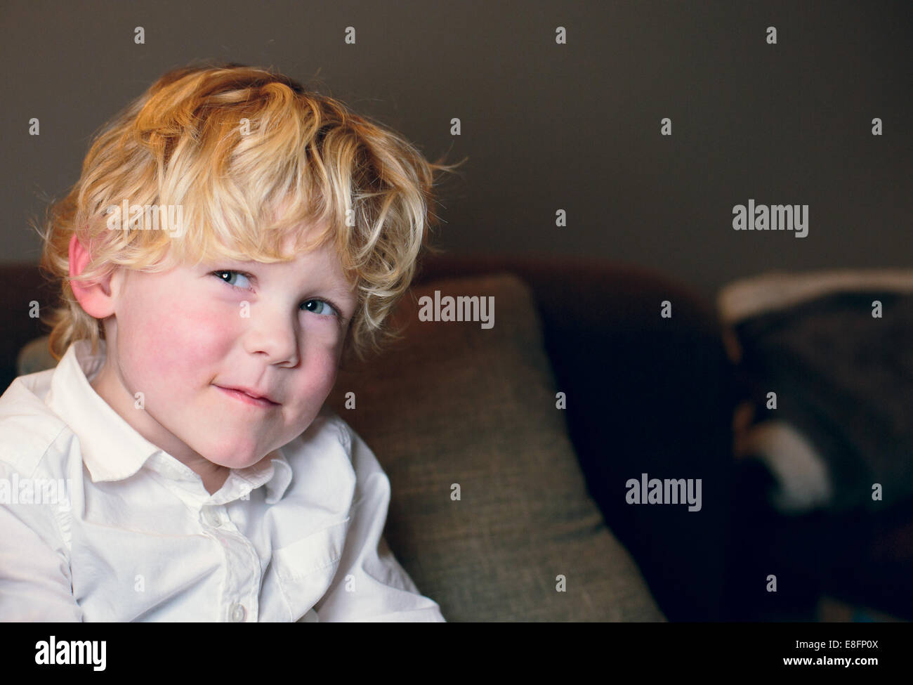Netherlands, Blonde boy (4-5) in white shirt smiling - Stock Image