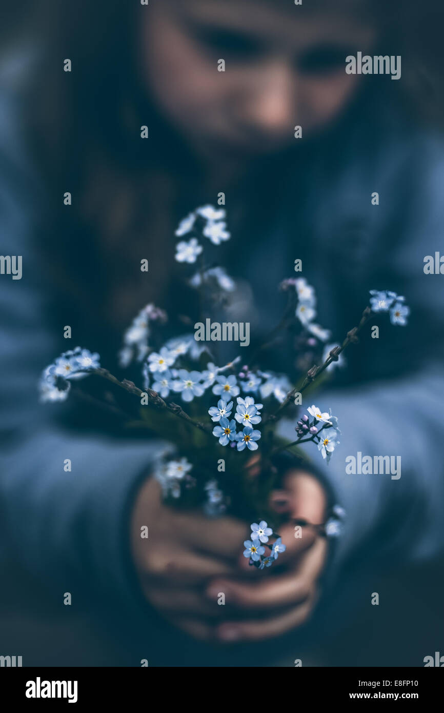 Norway, Girl (8-9) holding bouquet of forget-me-not flowers Stock Photo