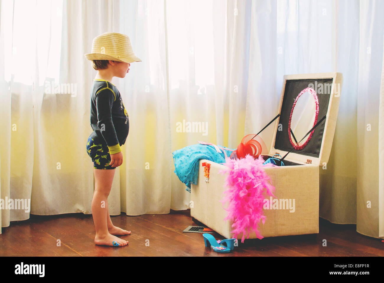 Boy  (2-3) wearing large hat standing by dressing up box - Stock Image