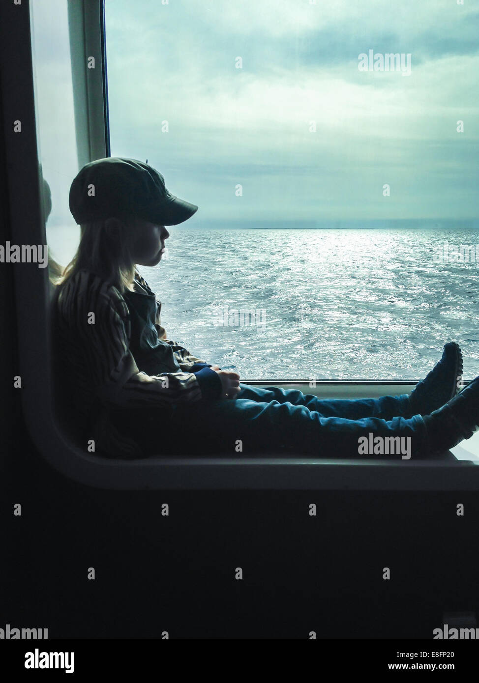 Side view of boy sitting in  window on ferry - Stock Image