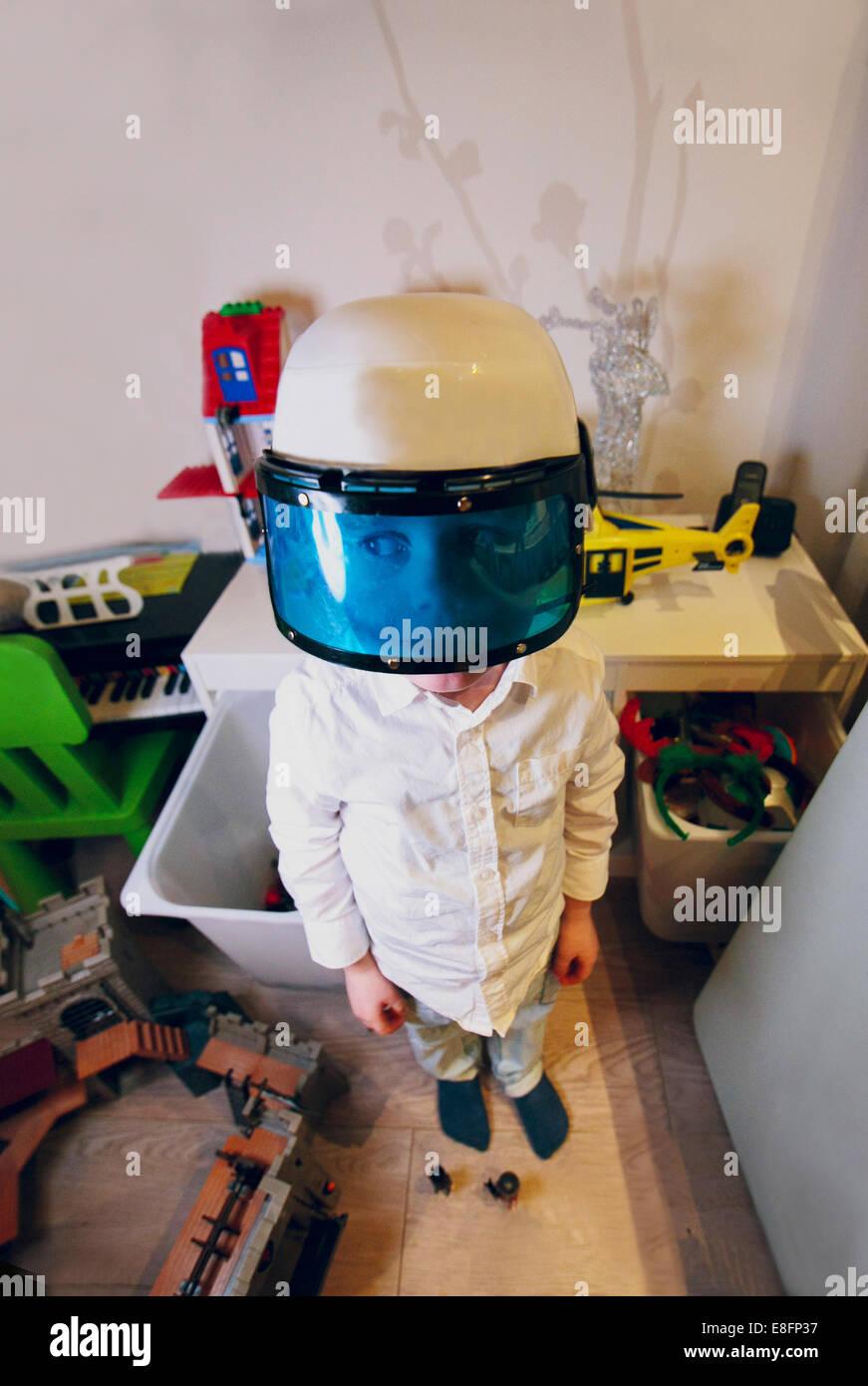 Netherlands, Boy (4-5) wearing policeman's helmet with visor - Stock Image