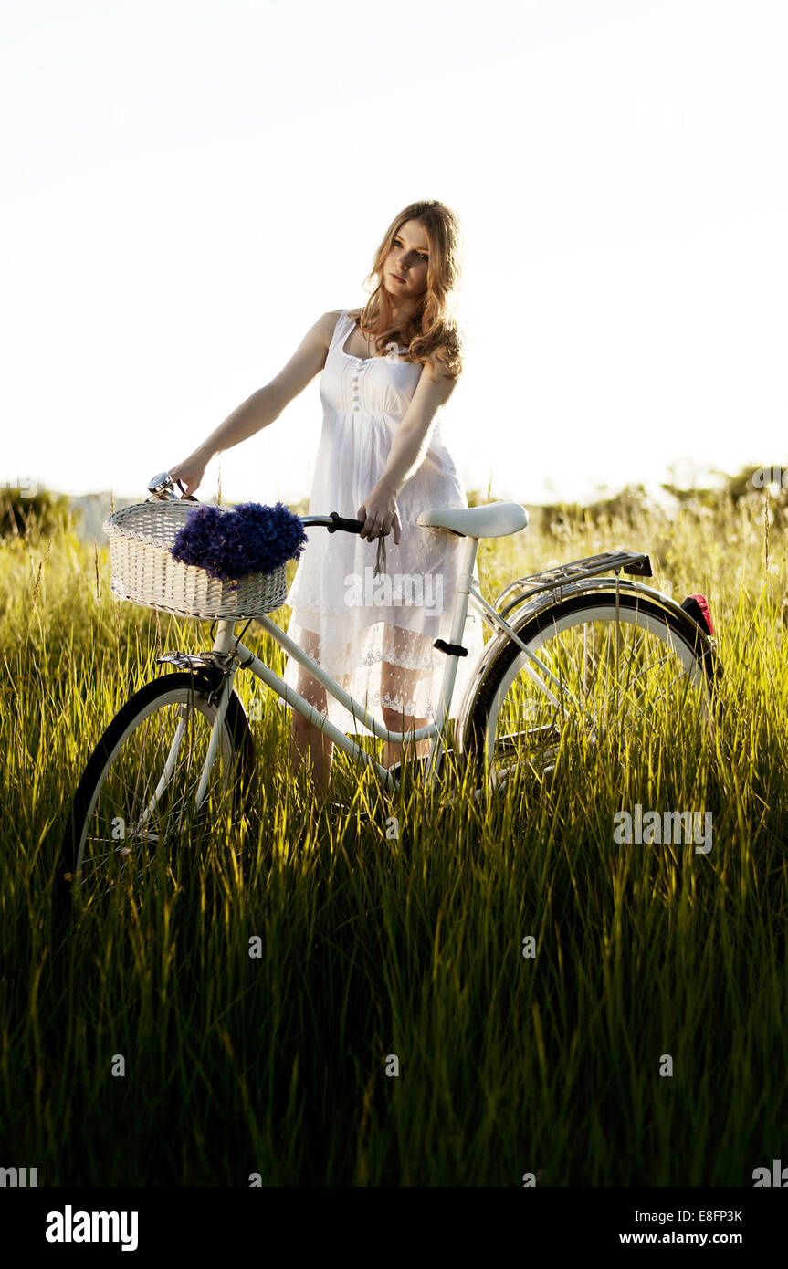 Young adult women standing with bicycle - Stock Image