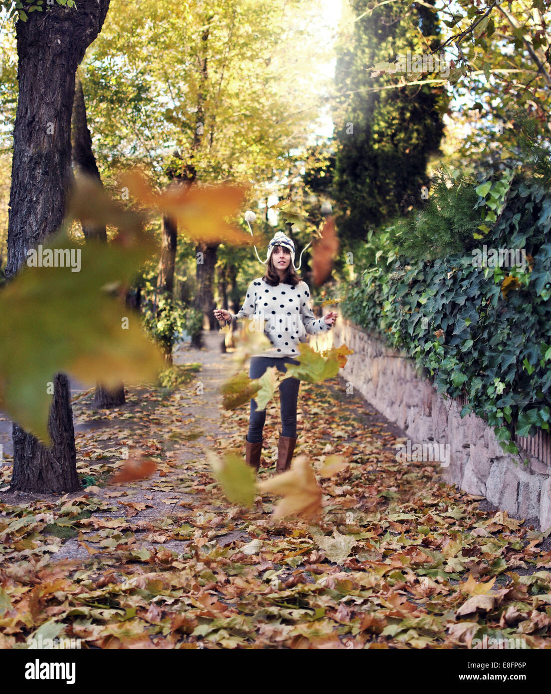Woman standing throwing autumnal leaves in park - Stock Image