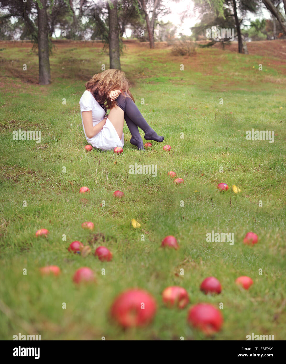 Woman sitting in a garden next to fallen apples, Spain Stock Photo