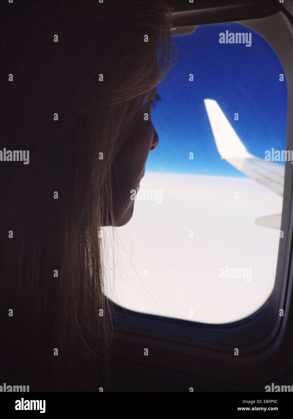 Woman looking out of window on a plane Stock Photo