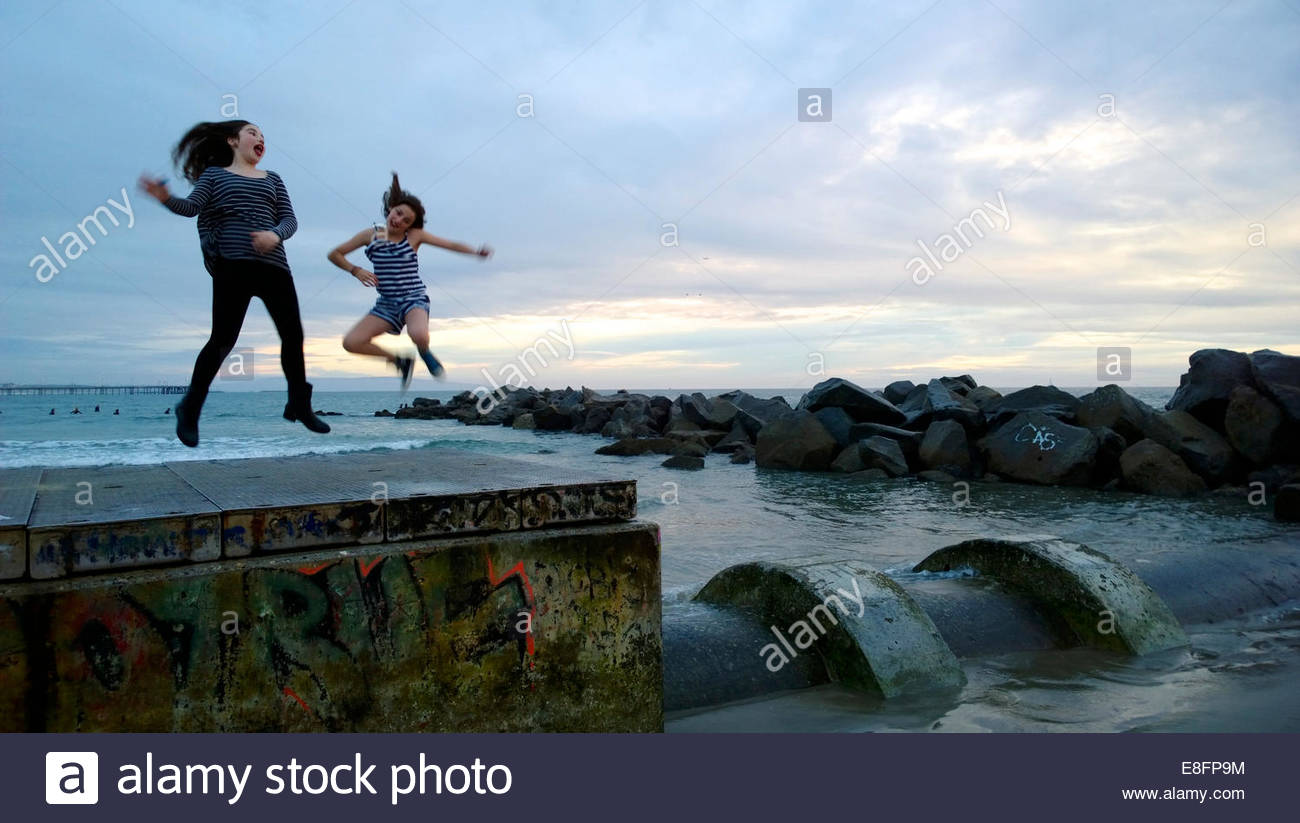 Two girls (10-11) jumping in air by beach - Stock Image
