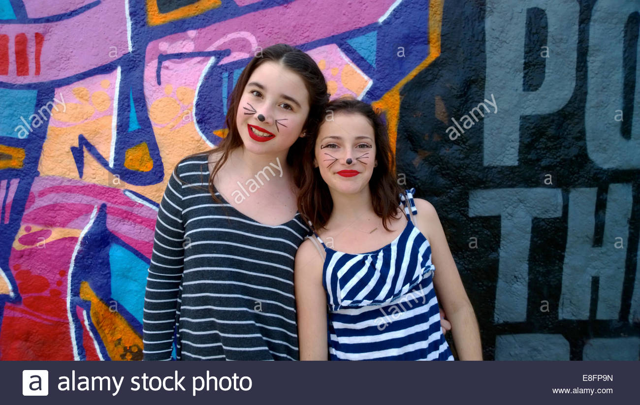 Two girls (10-11) with painted faces by graffiti covered wall - Stock Image