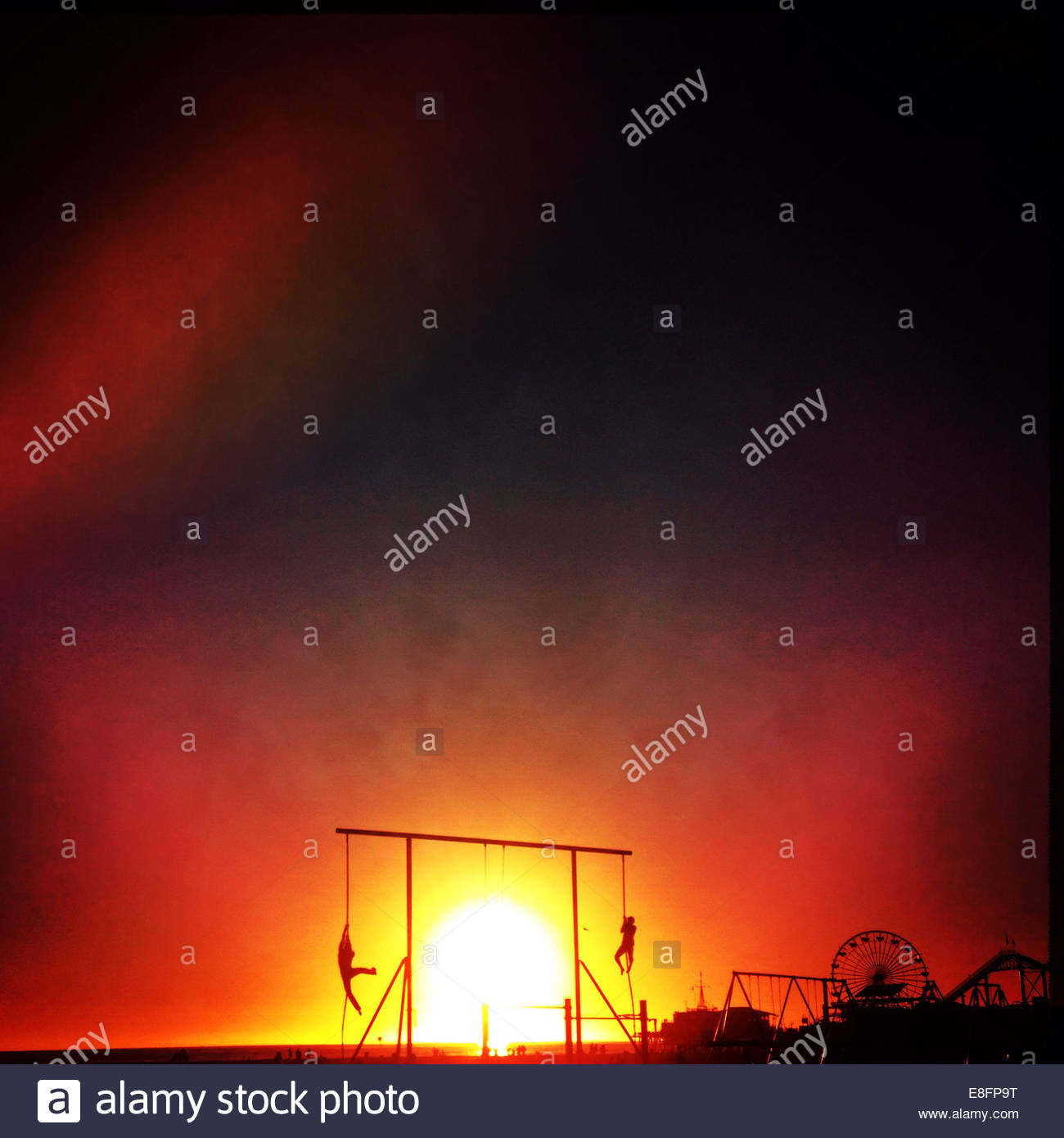 USA, California, Santa Monica, Silhouette of muscle park and pier at sunset - Stock Image